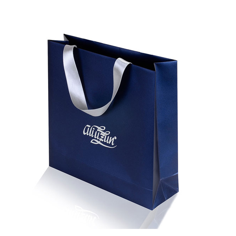 blue paper bag with ribbon handle