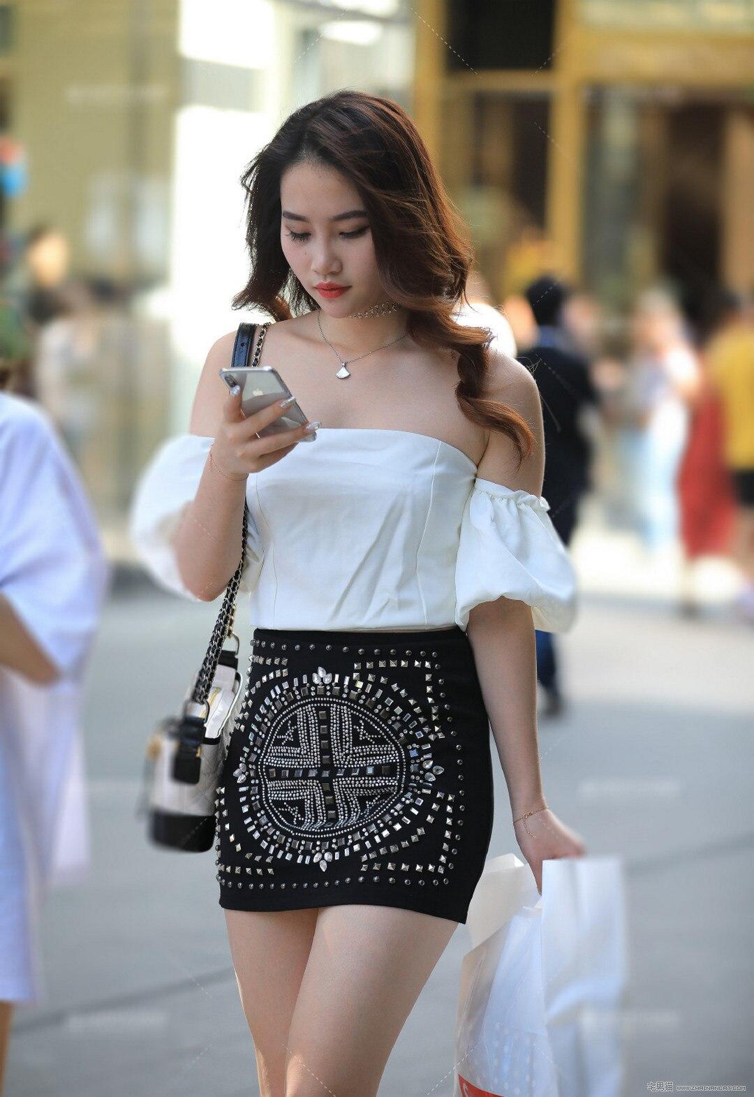 街拍:专注玩手机的小姐姐裙子也太好看了吧