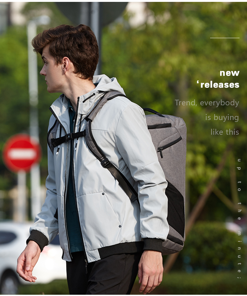 a guy carrying a grey backpack