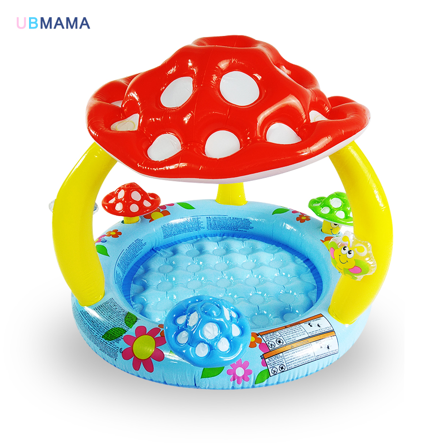 Children at the bottom of an inflatable swimming pool with baby mushroom awning pool sea pool basin<br>