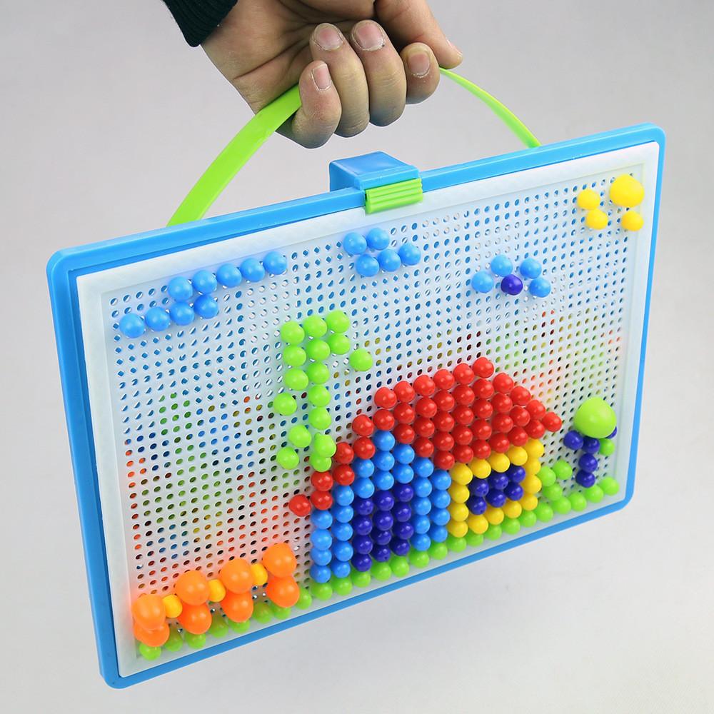 Mão segurando o tabuleiro do mosaico com pequenas peças coloridas