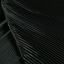 Garment fabric of pure black pinstripe accordion pleated silk satin crushed through dress fabric