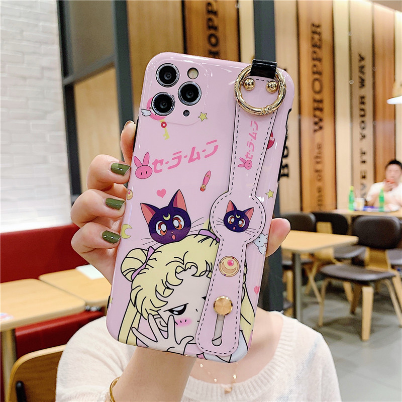 Sailor Moon Luna Soft iPhone Case With Wrist Strap Bracket A popular accessory where function and fashion come together, this Sailor Moon Luna Soft iPhone Case With Wrist Strap Bracket not only protects your Apple iPhone Series cell phone from the wear and tear of daily use, its colors and designs also help to reflect your distinctive styles and moods. Available in an eye-catching pink/white color that helps a standard mobile device to stand out from the pack with style. The high-quality mobile case brings a personal touch to any model from the Apple iPhone Series, while adding valuable protection to the device. Offering an unmatched viewing experience that also protects the phone from damage, the glossy finish is great for people who take photos or watch videos on the go. The tempered, scratch-resistant glass repels oily residue, installs easily and provides an extra-thin layer of security.