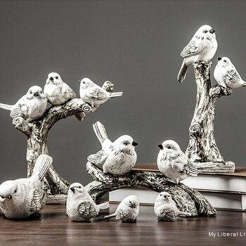 Estatuillas de pájaros de resina posados en ramas