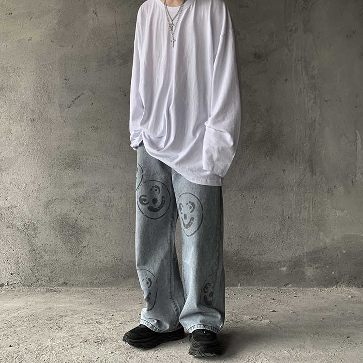 ใบหน้ายิ้มพิมพ์กางเกงยีนส์บุรุษ Streetwear Hip Hop หลวมตรงขี้เกียจกางเกงยีนส์เก่าโรงเรียน Graffiti DENIM กางเกง