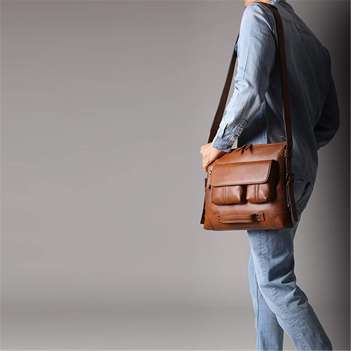 a guy walking with a leather shoulder bag