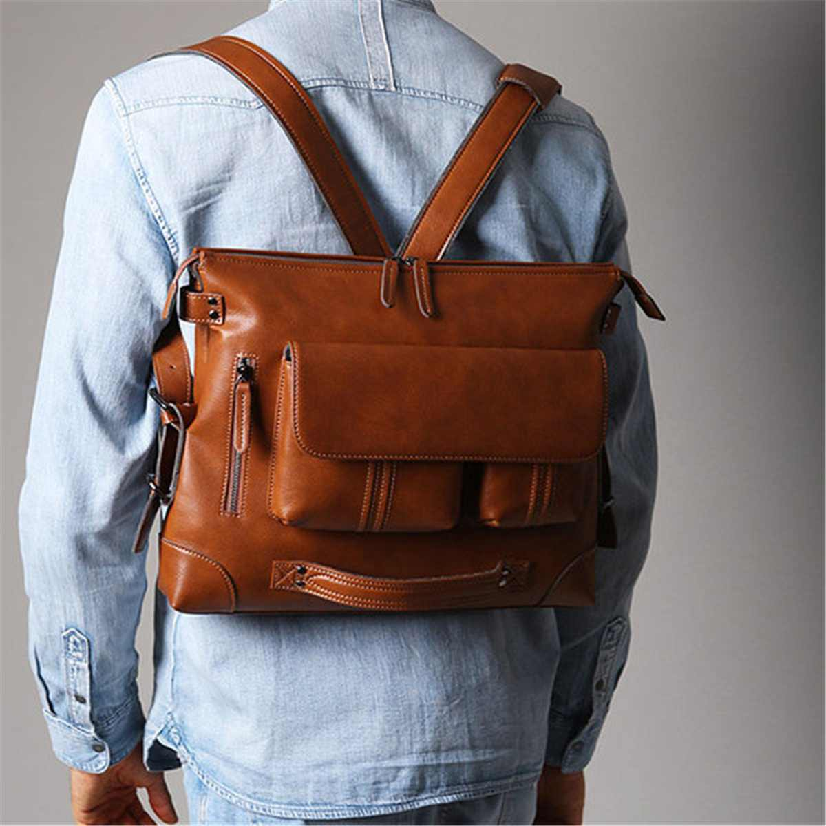 a guy carrying a leather shoulder bag