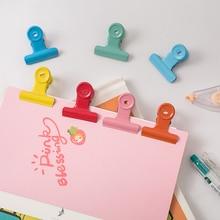 Красочные металлические зажимы отмечает письмо бумага офиса студент поставляет цвет случайный обязательного зажимы