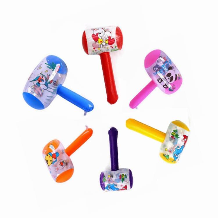 Les enfants battent la boule gonflable avec le marteau gonflable de jouet de cloche