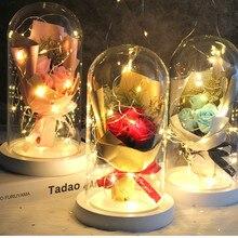Um pacote de flores artificiais de rosa vermelha em um domo de vidro em uma casa branca decoração para o dia dos namorados presentes presente do dia da mãe