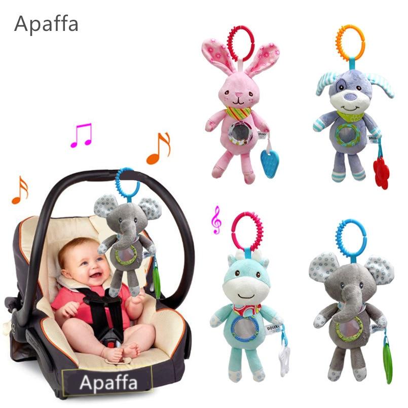 Beebi kõristab jalutuskäru, mis ripub pehmest mänguasjast, - Väikelapse mänguasjad