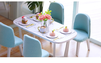 dining room of the blue doll house. table and chairs, the table is set with plates and cutlery