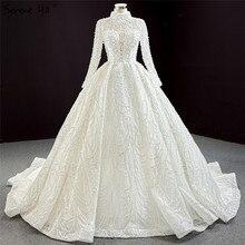 Luksusowe Ivory suknie ślubne na szyję Sexy Plus Size 2020 długie rękawy frezowanie suknie ślubne z perłami BHM67129 Couture Dress