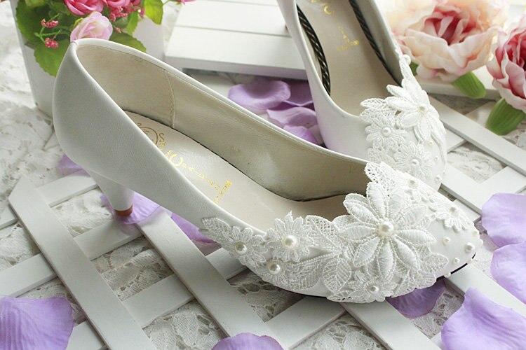 Sapatos de salto alto com flor branca,