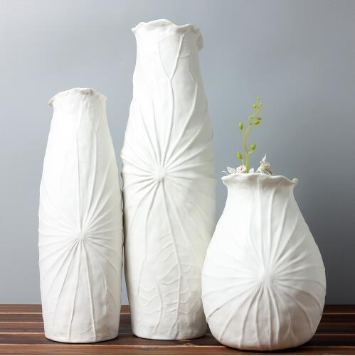 three white flower vases