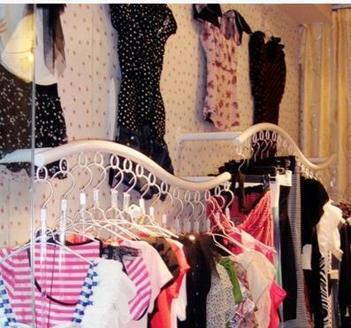 Lart de fer montre les supports de porte-vêtements dans un magasin de vêtements avec un anneau noir et blanc sur le mur