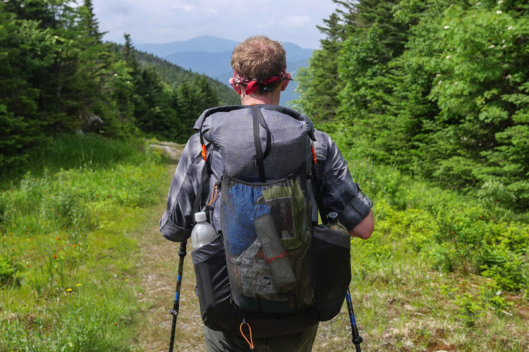 Man hiking in bush with 3F UL ultralight backpack.