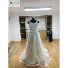 عاجي تول رقبة v الطول الأرضي فساتين الزفاف ذيل شابيل بلا أكمام فستان زفاف مخصص