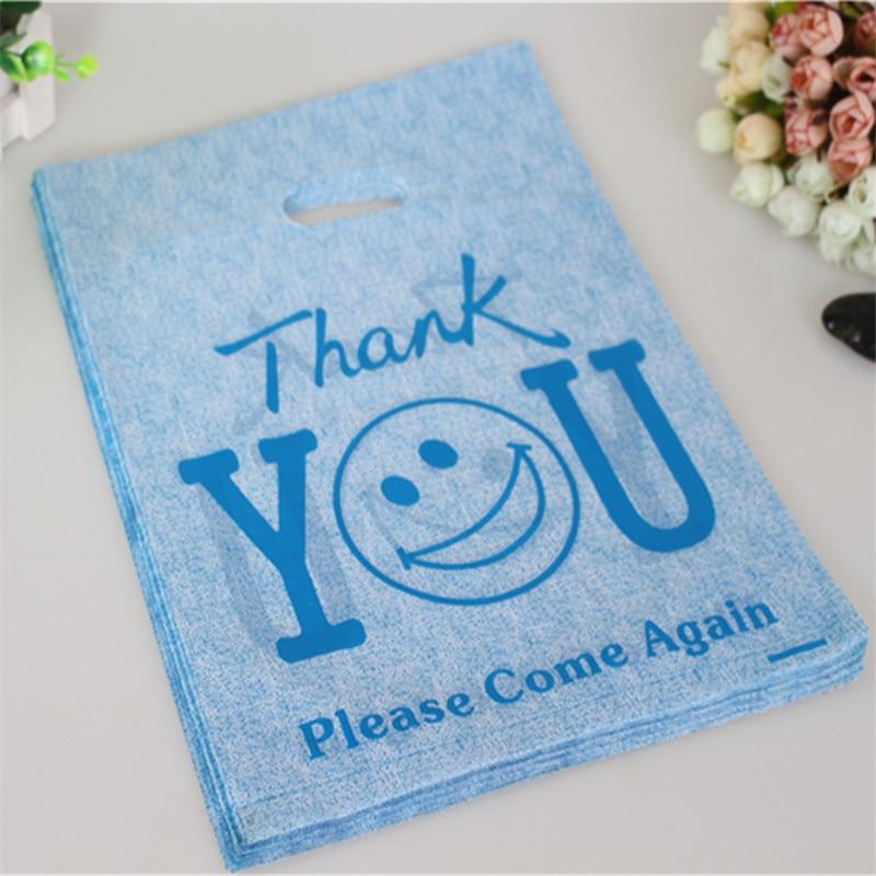 3c4ed235d Venta al por mayor caliente 100 unids/lote 25*35 cm Azul gracias sonrisa  Cara gran empaquetado Bolsas con mango regalo plástico Bolsas de tela