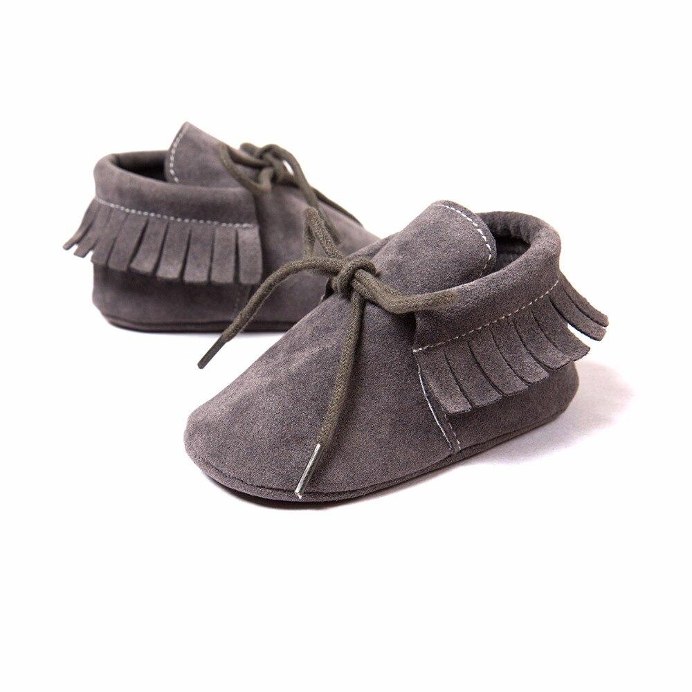 Los primeros andadores del bebé Bebe Fringe Suela suave Calzado antideslizante Zapatos de cuna Zapatos de bebé recién nacidos del cuero del ante de la PU