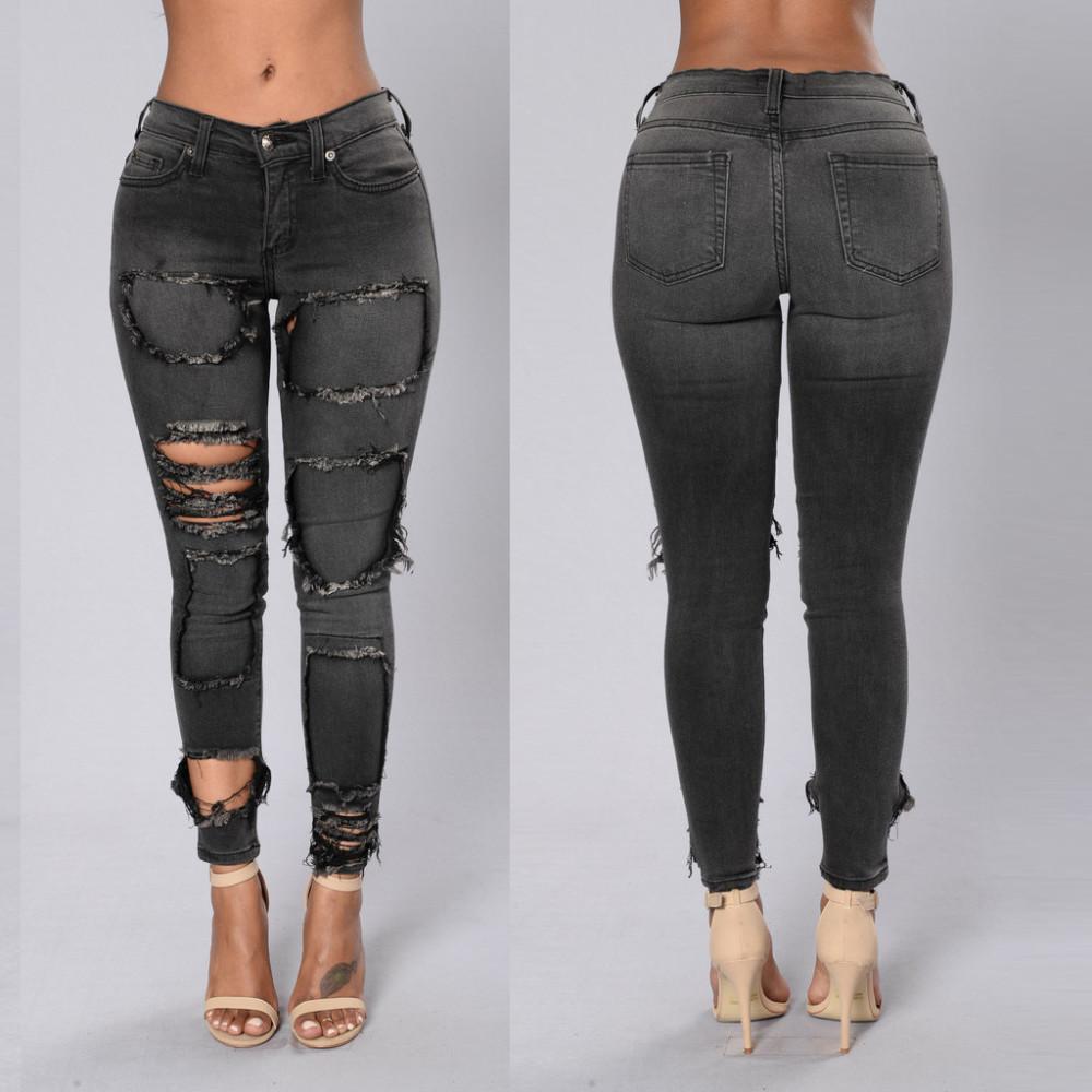 Tumehallid rebitud teksapüksid