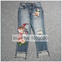 Роскошные Промытые джинсовые укороченные Рваные джинсы спереди Цветочный угол патч Украшенные нерегулярные манжеты задние карманы Коротк