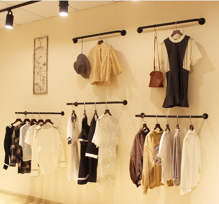 Un présentoir pour un fer à repasser vêtements magasin. un mur cintre pour vêtements pour femmes. le u-forme est suspendu sur le côté .. 1106