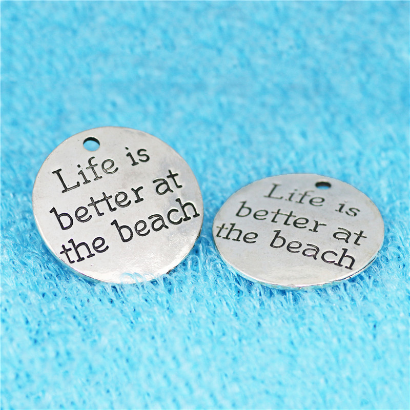 Top Quality 10 Pcs/lot Diameter 23mm Life is better at the beach Antique Silver Round Disc Quote Message Charms Pendant