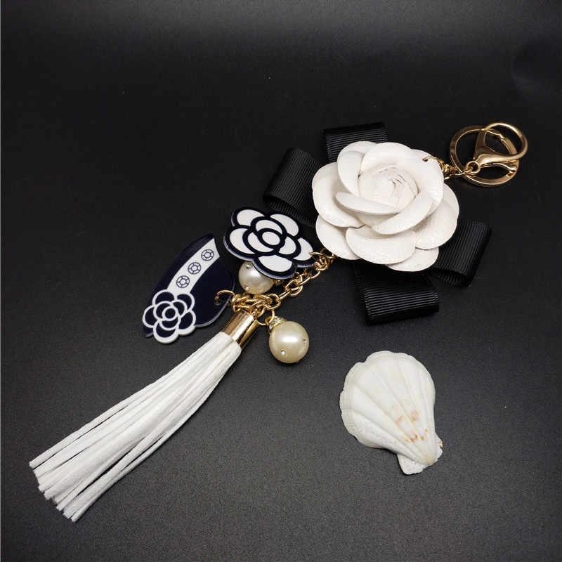 עור אמיתי שחור ולבן זכר ונקבה Keychain תיק בפלאש רכב מפתח טבעת רכב מפתח קמליה פרח כובע ציצית סגנון מפתח שרשרת