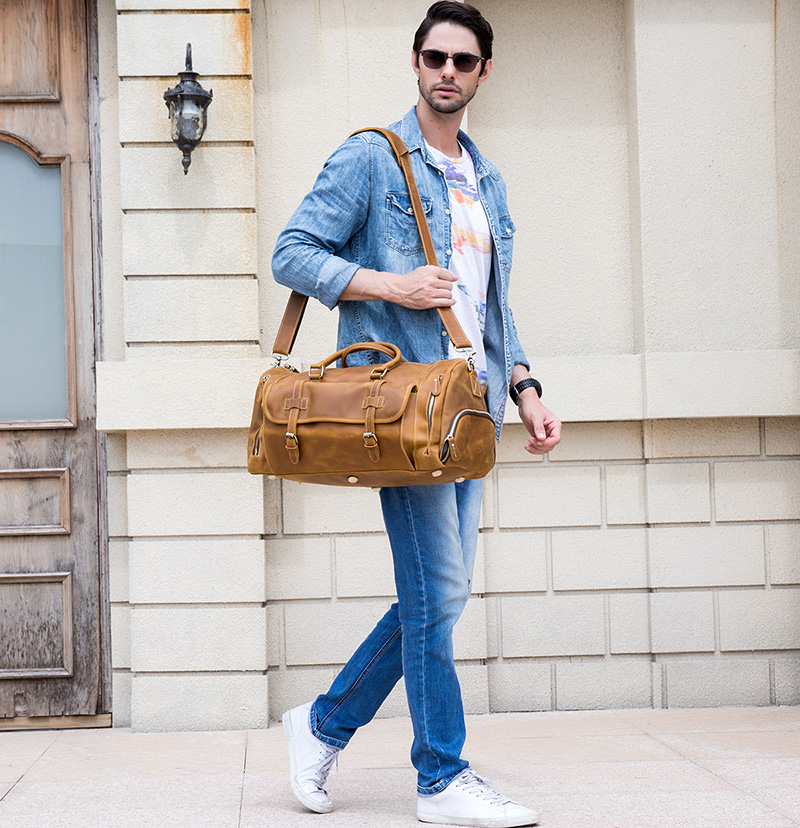 a guy carrying a vintage leather duffle on the street