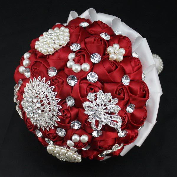 crimson bride holding flowers decorated with pearls diamond ribbon