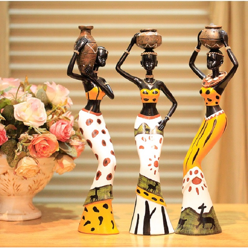 3 figurines of african woman in gold and white dresses