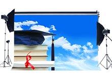 Fondo de telón de fondo de la ceremonia de graduación con el título y el fondo de la gorra de Trencher libros azul cielo blanco nube de fondo