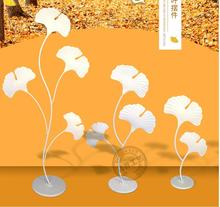 The new iron art ginkgo biloba road leads to the wedding decorations and props table.