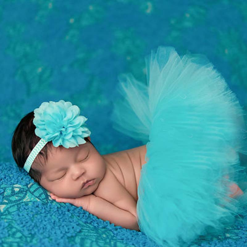 Headshot of a sleeping 8 day old newborn baby girl wearing a pink tutu and rhinestone headband. She is sleeping on her tummy on a white billowy blanket. Portrait of a beautiful very young girl, in a dance school wearing a white tutu, she trains alone to learn new dance steps.