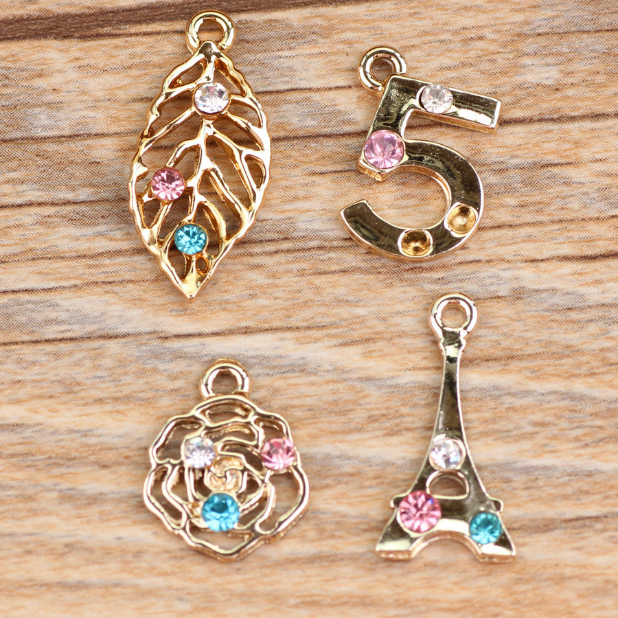 1ee81050c321 Wholeslae moda surtidos 50 unids Hallow out oro tono Diamantes con piedras  falsas hoja pavimentada number 5 Rosa flor Torre Eiffel joyería Amuletos