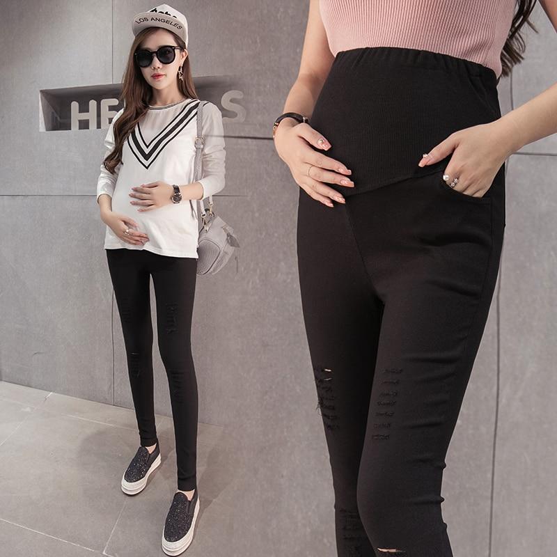 गर्भवती महिलाओं के जींस पैर पेंसिल पैंट पतली छेद वाले डेनिम पैंट बड़े गज की दूरी पर ढीले पेट के साथ एक व्यक्ति की खेती करते हैं