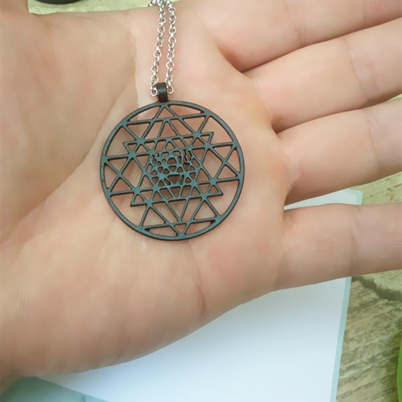 Collier Sri Yantra en métal peint en noir, laqué, chaîne et pendentif, symbole zen, bijou spirituel tendance yoga, dans une main
