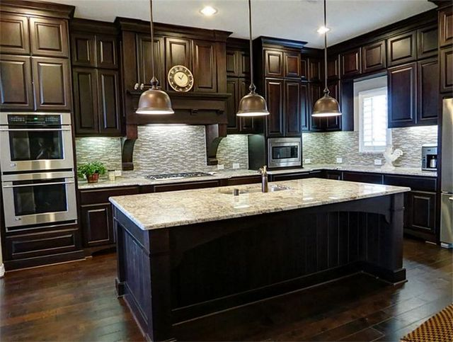 Solid Wood Kitchen Cabinet With A Breakfast Bar And Bar Chairs In