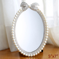 Shiny Silver Plating with White Pearls and Clear Rhinestones Jeweled Ribbon Design 5x7 inches Oval Metal Framed Tabletop Mirror