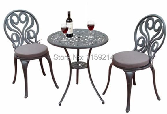 Une table et deux chaises meubles de jardin noir balcon for Table exterieur fonte