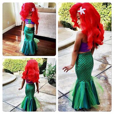 ילדה בתחפושת בת הים הקטנה שכוללת חלק תחתון סנפיר ירוק, ביקיני סגול ופאה אדומה עם כוכב ים