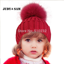 Телая вязанная детская шапка с помпоном из меха енота.
