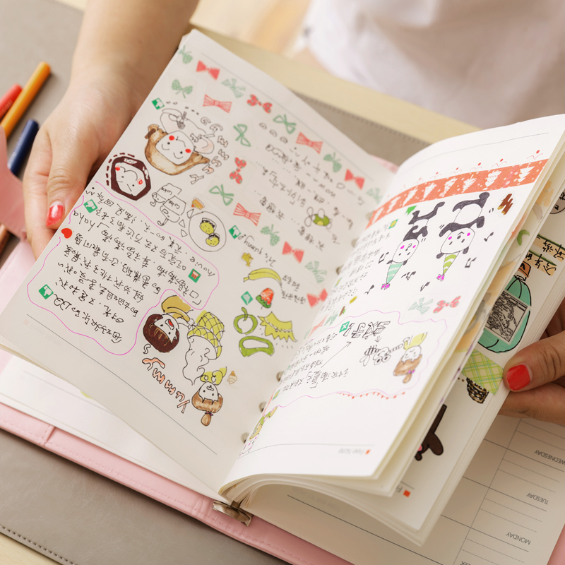 person holding a cute planner with cartoons and colorful designs