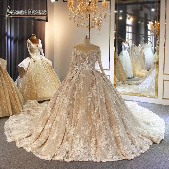 فستان زفاف بلون الشمبانيا مع قطار طويل فاخر وزهور ثلاثية الأبعاد