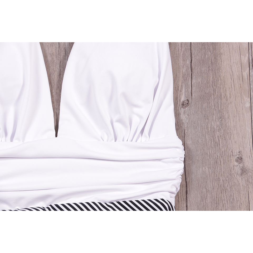 Foto of upper part of white color new one piece swimsuit for beach. Swimming backless v-neck for women