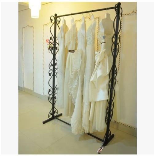 Hierro forjado doble ropa colgada en rack en la plataforma de la ...