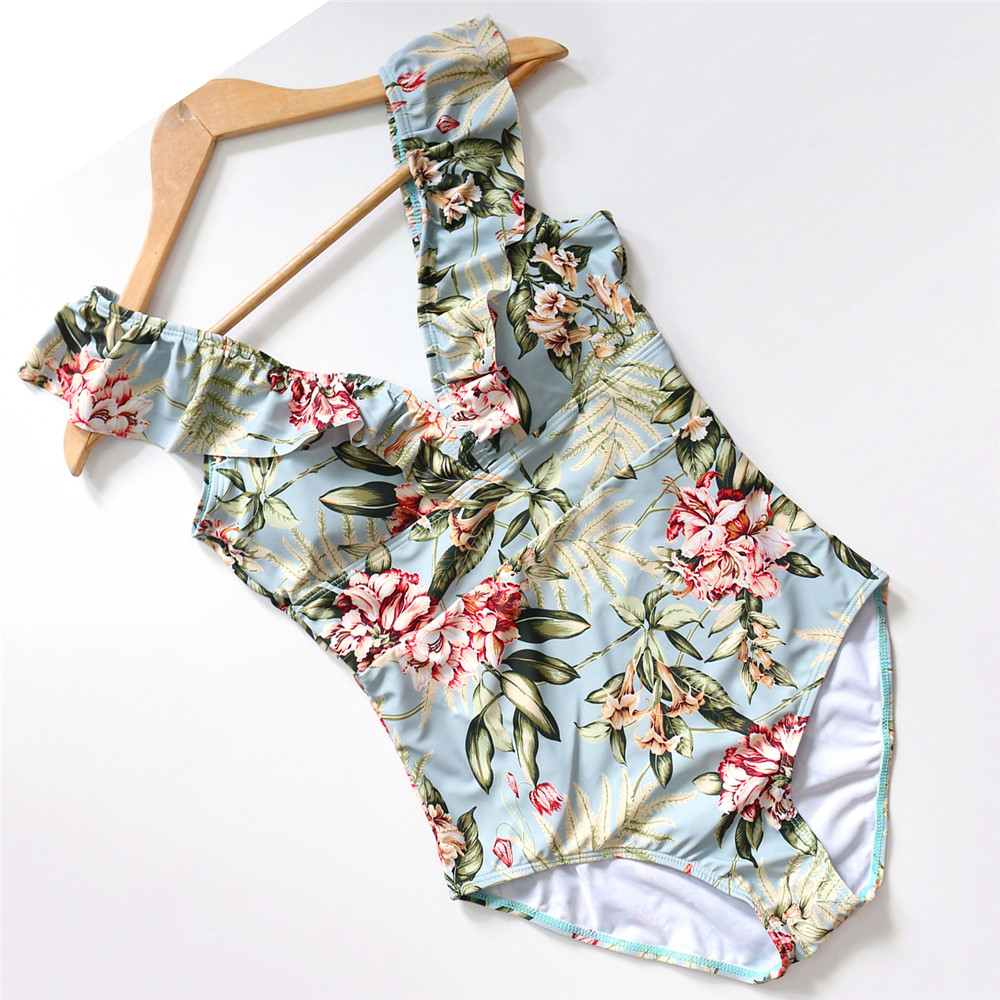 Foto of flower print from the top women's one-piece v-neck swimsuit. Female one-piece swimwear for swimming pool