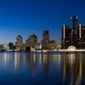 Buildings in a city lit up at dusk  Detroit River  Detroit  Michigan  USA Poster Print (36 x 12)