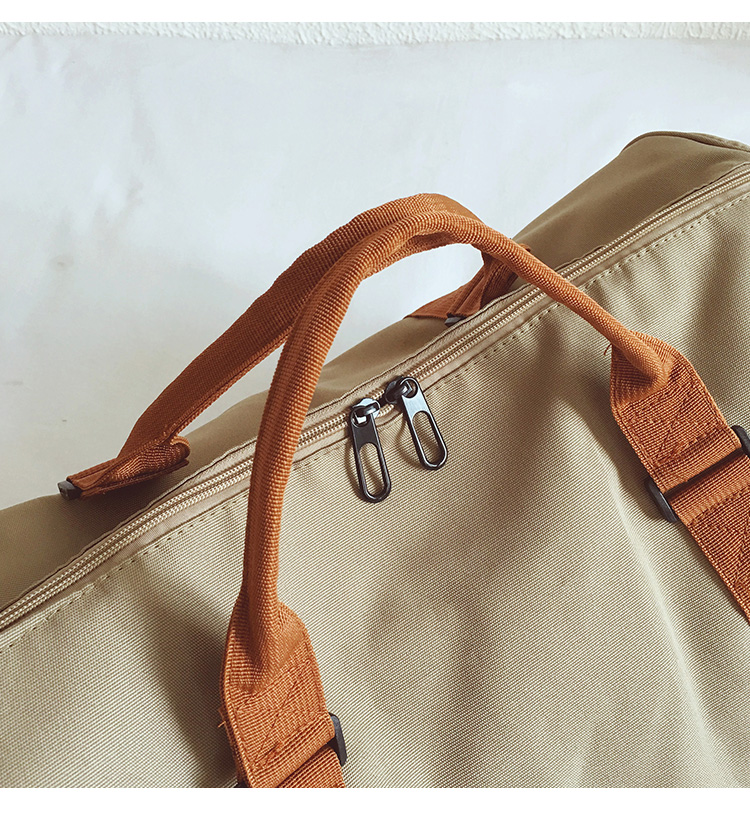 a photo of the brown handle of a beige duffle